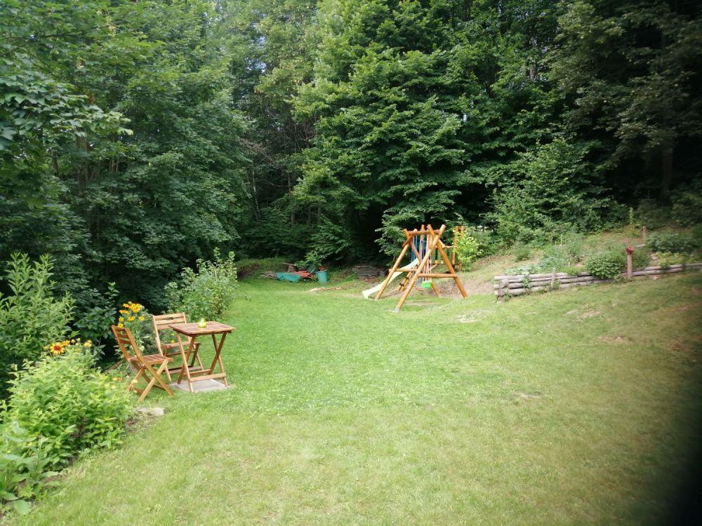 Zadní část zahrady s posezením a houpačkami